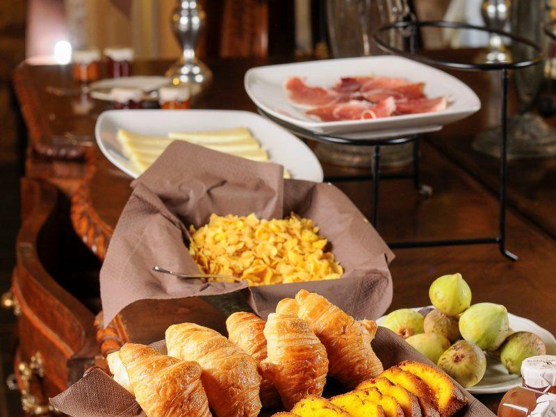 bufet desayuno con frutas, bollería embutidos y queso